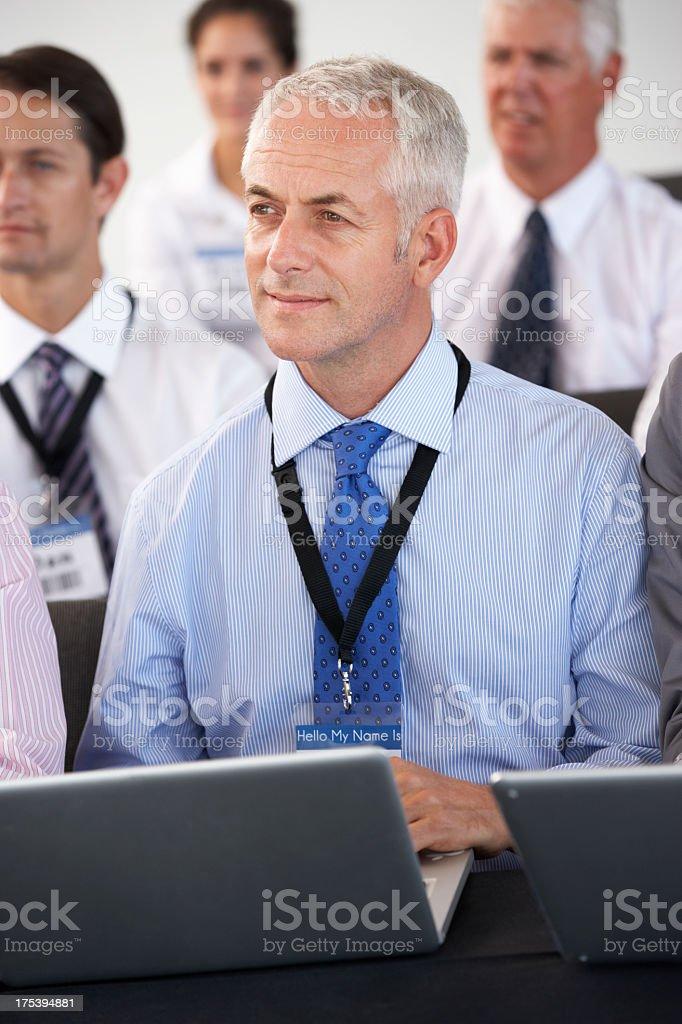 Male Delegate Listening To Presentation stock photo