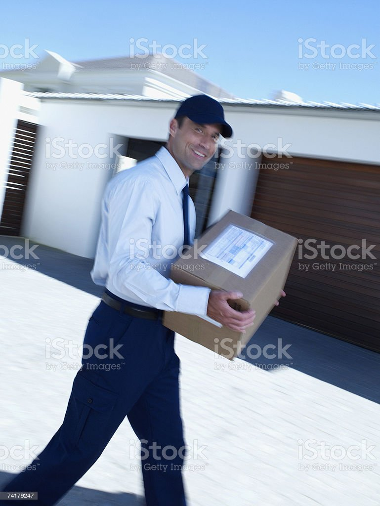 Male delivery person in cap walking with box royalty-free stock photo