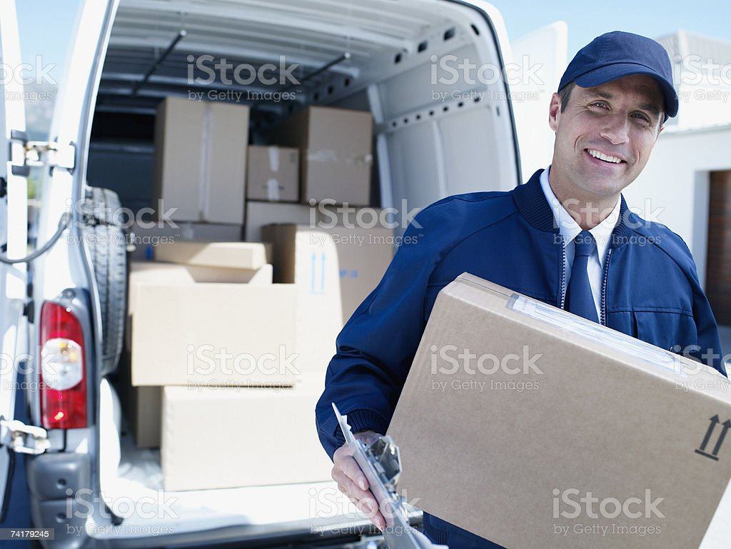 Male delivery person in cap with van and boxes stock photo