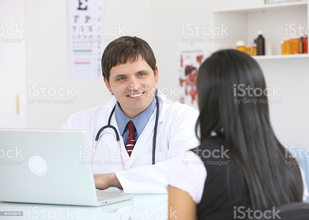 Male doctor consulting with female patient royalty-free stock photo