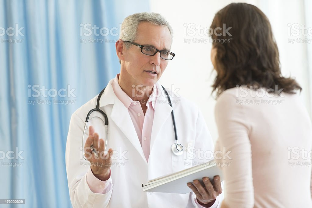 Male Doctor Discussing With Patient In Clinic stock photo