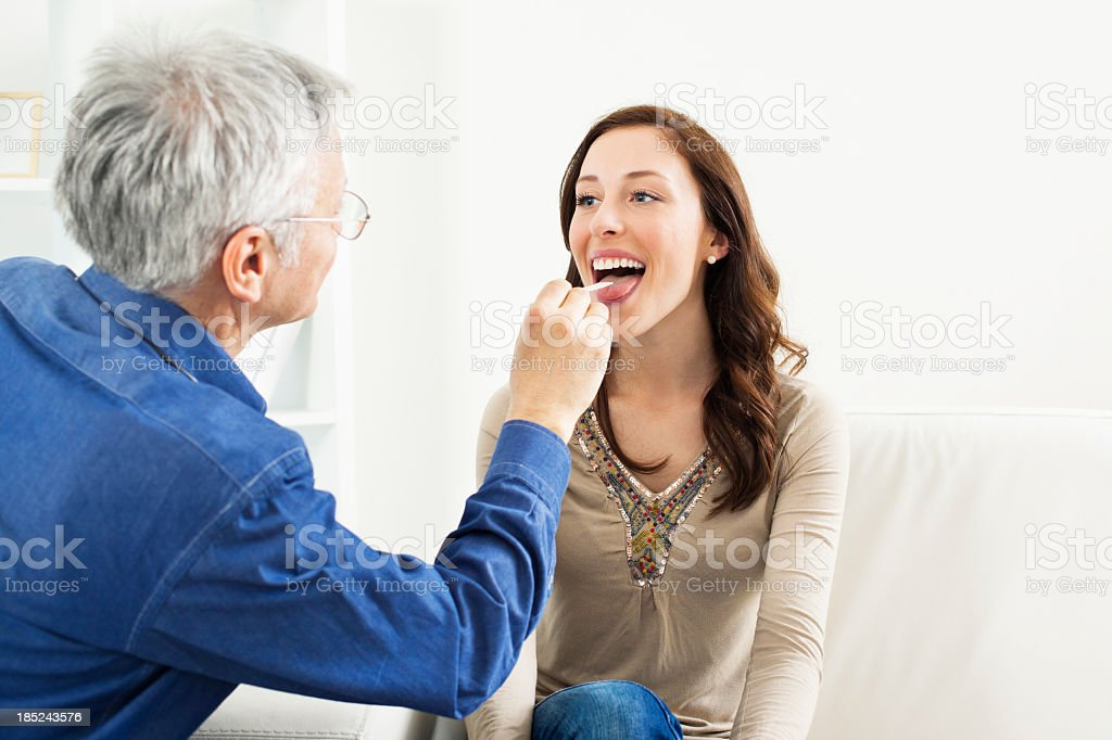 Male Doctor Doing Throat Exam To Woman stock photo
