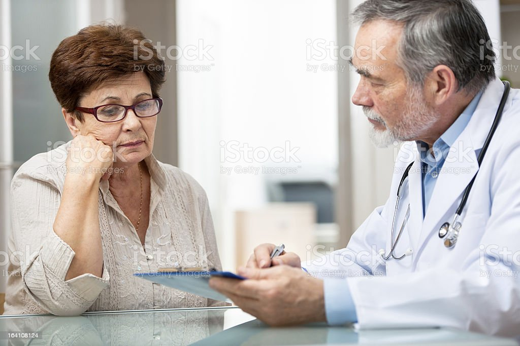 Male doctor explaining something to female patient stock photo