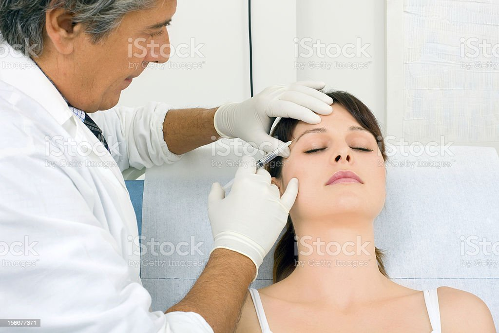 A male doctor giving a female patient Botox injections stock photo