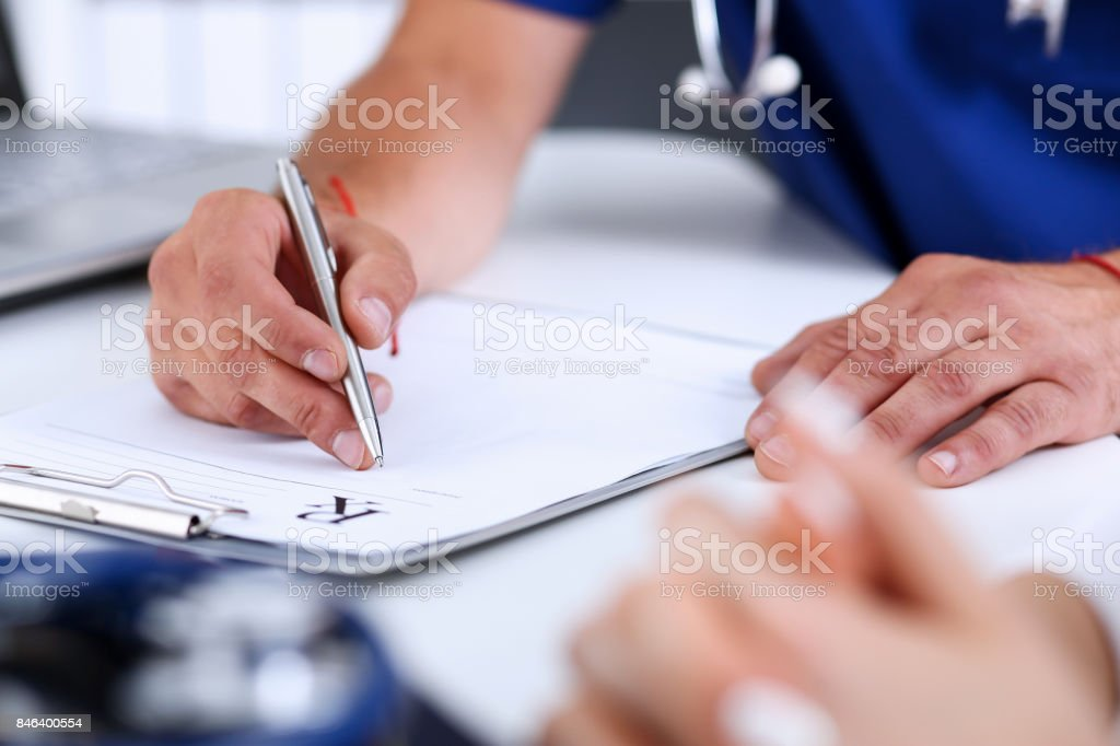 Male doctor hand write prescription at office worktable stock photo