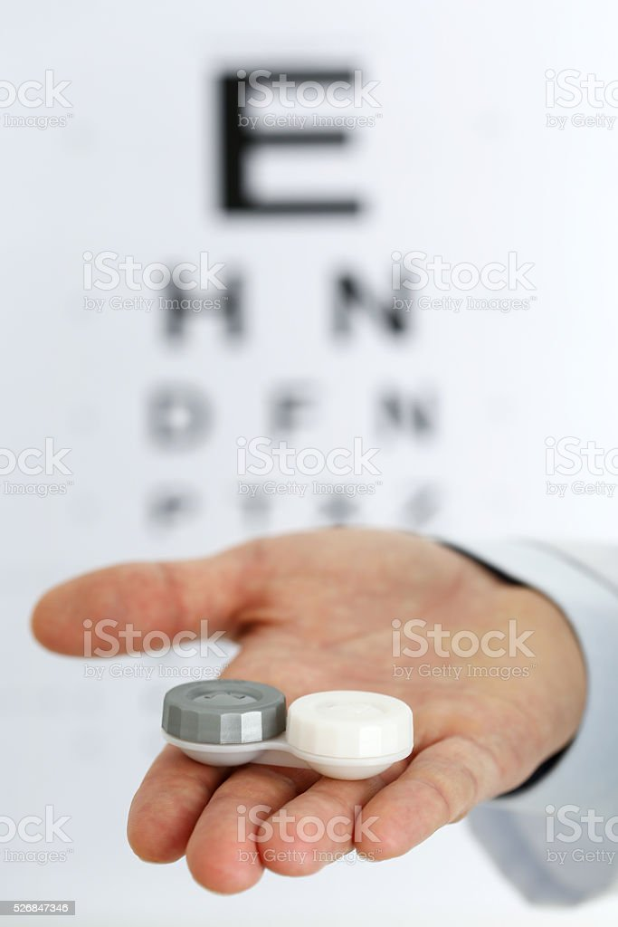 Male doctor hands giving pair of contact lens stock photo