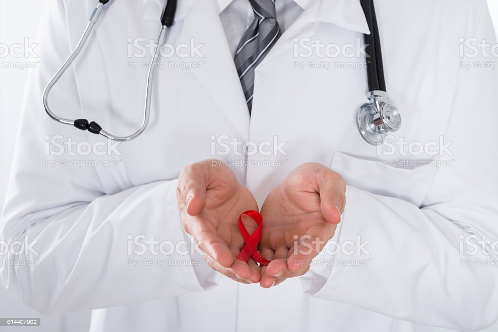 Male Doctor Holding Aids Ribbon stock photo