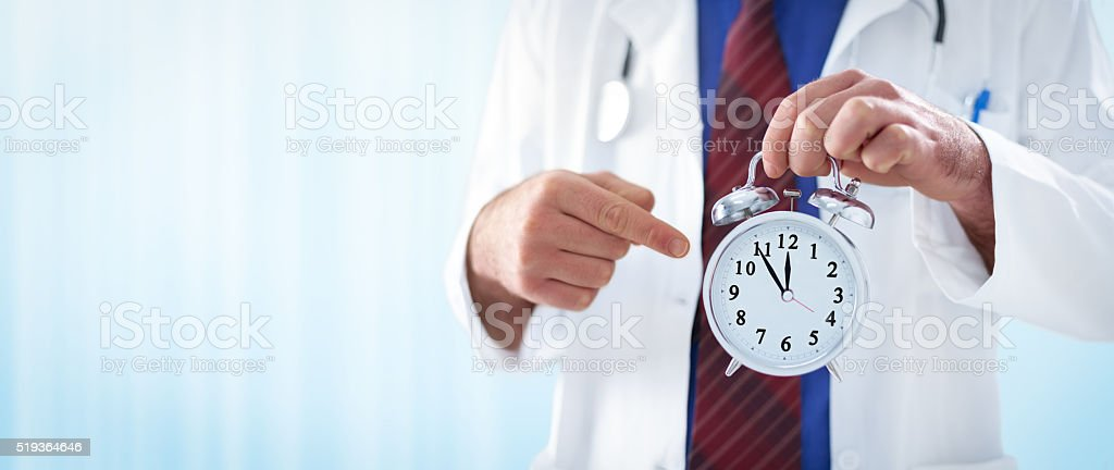 male doctor holding an alarm clock stock photo