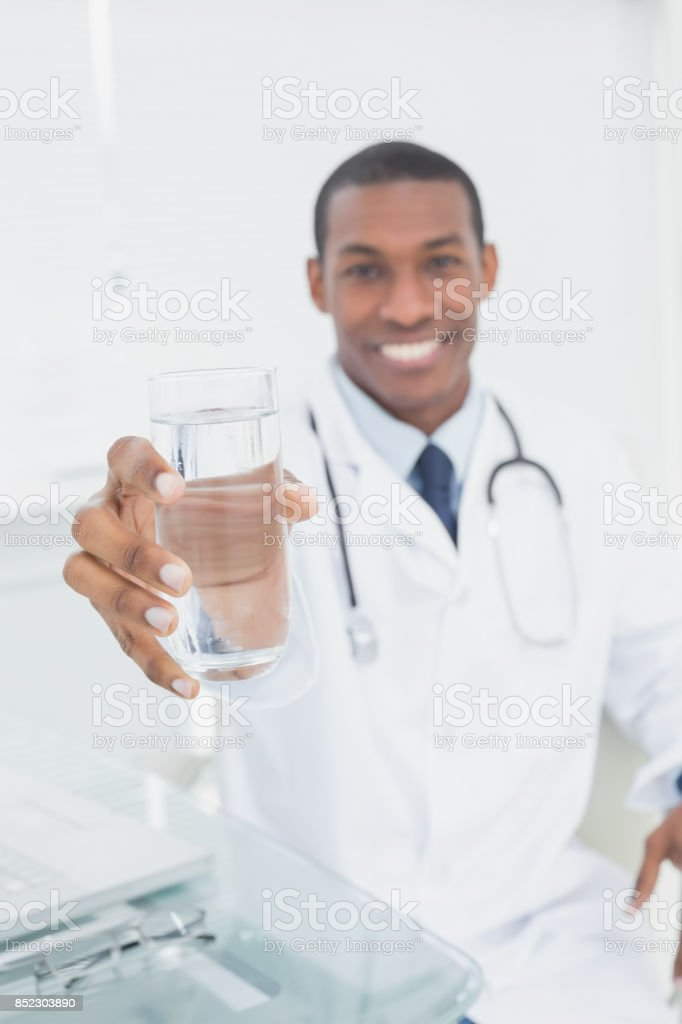 Male doctor holding out a glass of water in medical office stock photo