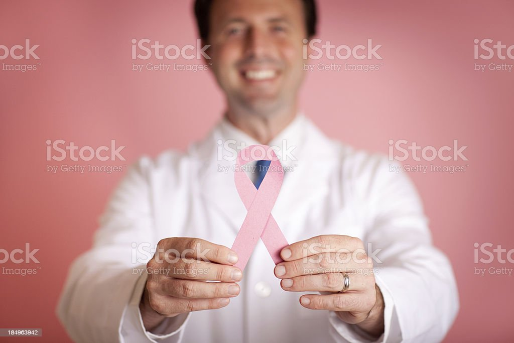 Male Doctor Holding Pink Breast Cancer Awareness Ribbon stock photo