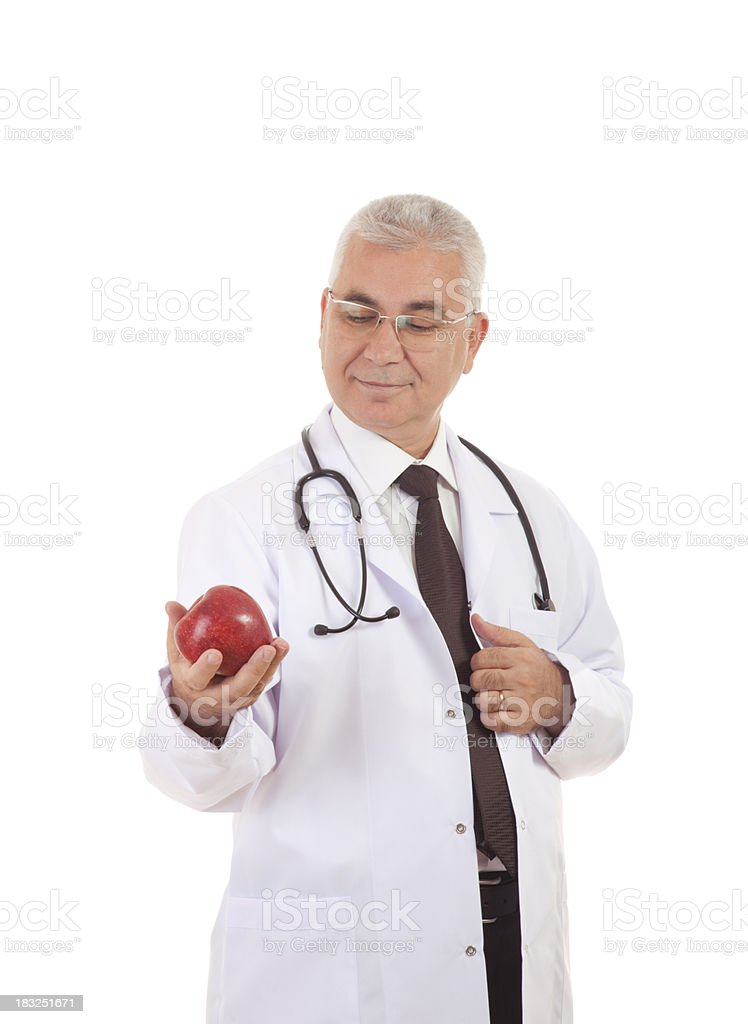 Male doctor holding red apple against white background royalty-free stock photo