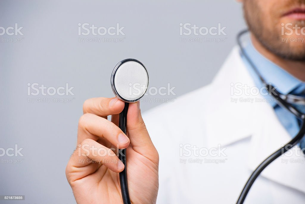 Male doctor holding stethoscope stock photo