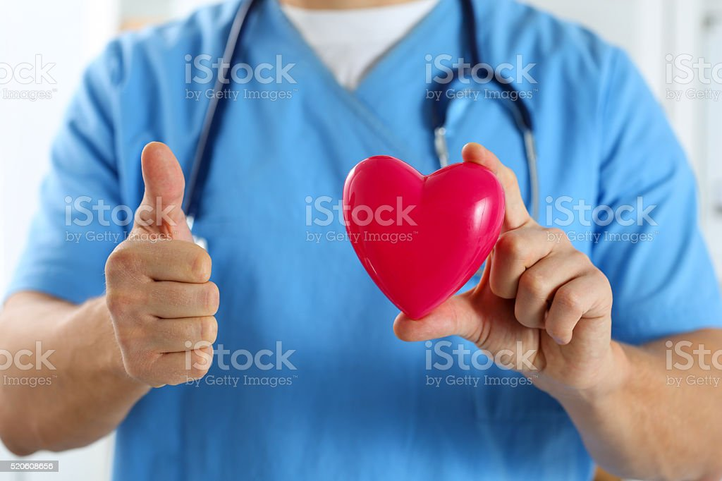Male doctor in blue uniform hold red toy heart stock photo