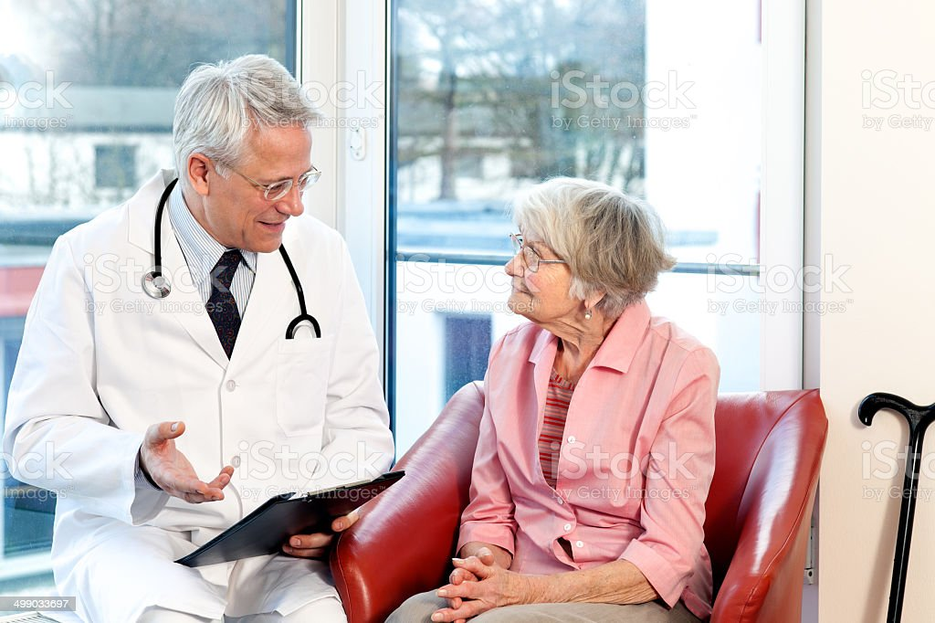 Male doctor in consultation with a senior patient. stock photo