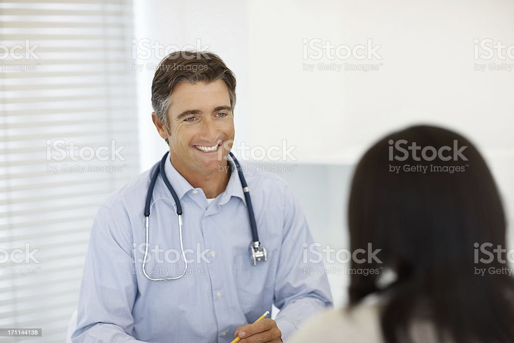 Male doctor in discussion with a woman at clinic royalty-free stock photo