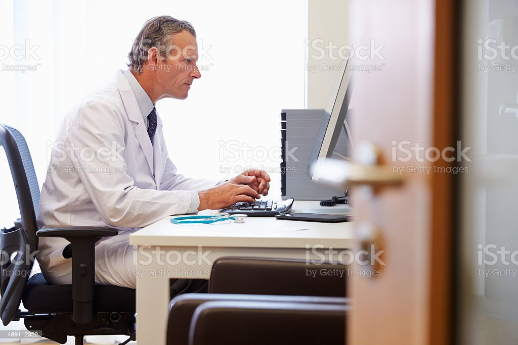 Male Doctor In Office Working At Computer stock photo