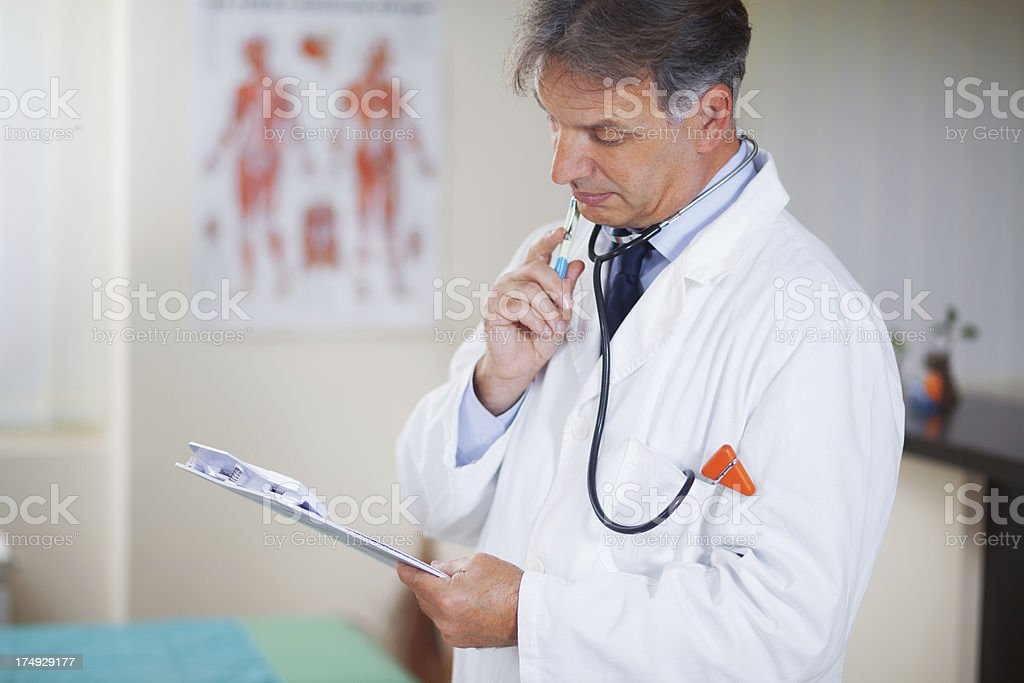 Male doctor looking at medical report stock photo
