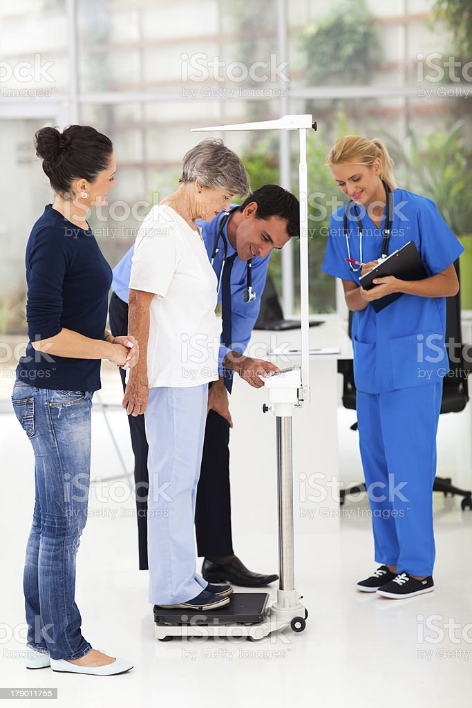 male doctor measuring patient's height and weight on scale royalty-free stock photo