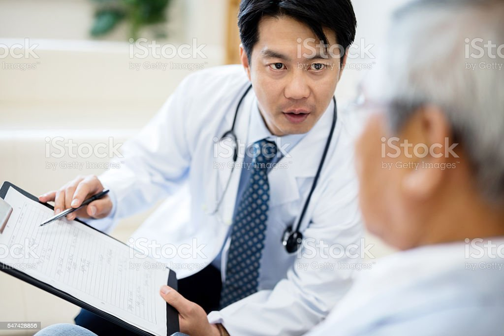 Male doctor showing record and explaining senior patient stock photo