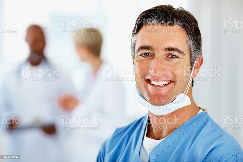 Male doctor smiling with colleagues in the background royalty-free stock photo