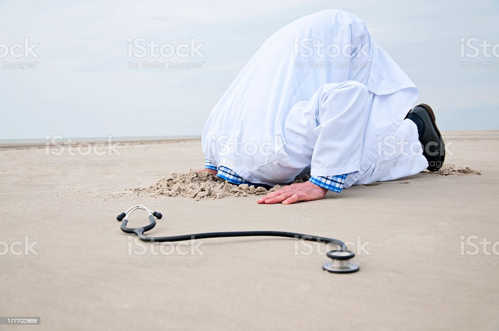 Male Doctor stucks Head in Sand stock photo