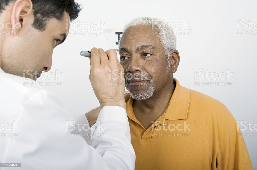 Male Doctor Testing Patient's Eye In Clinic stock photo
