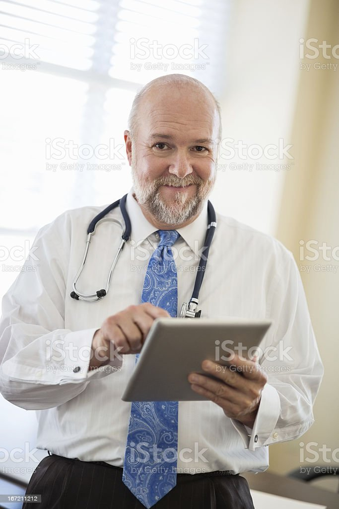 Male Doctor Using Digital Tablet In Clinic royalty-free stock photo