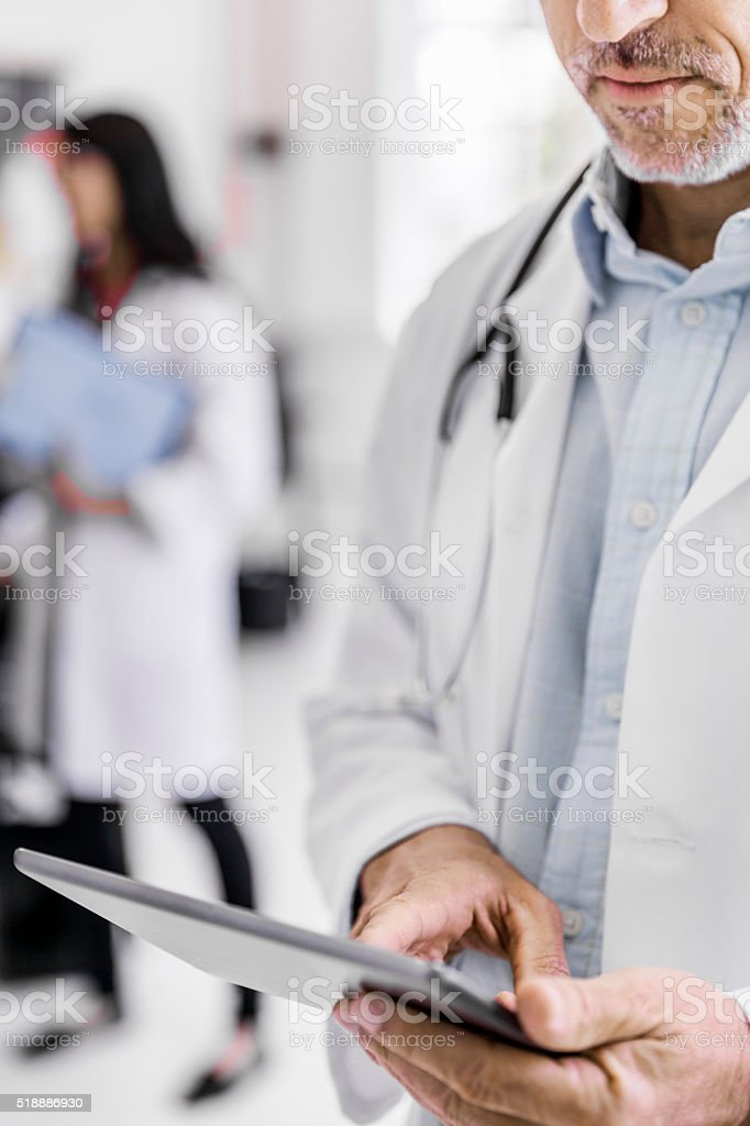 Male doctor using digital tablet in clinic stock photo