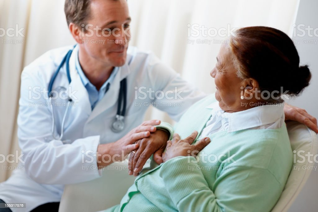 Male doctor visiting a senior woman at bed royalty-free stock photo