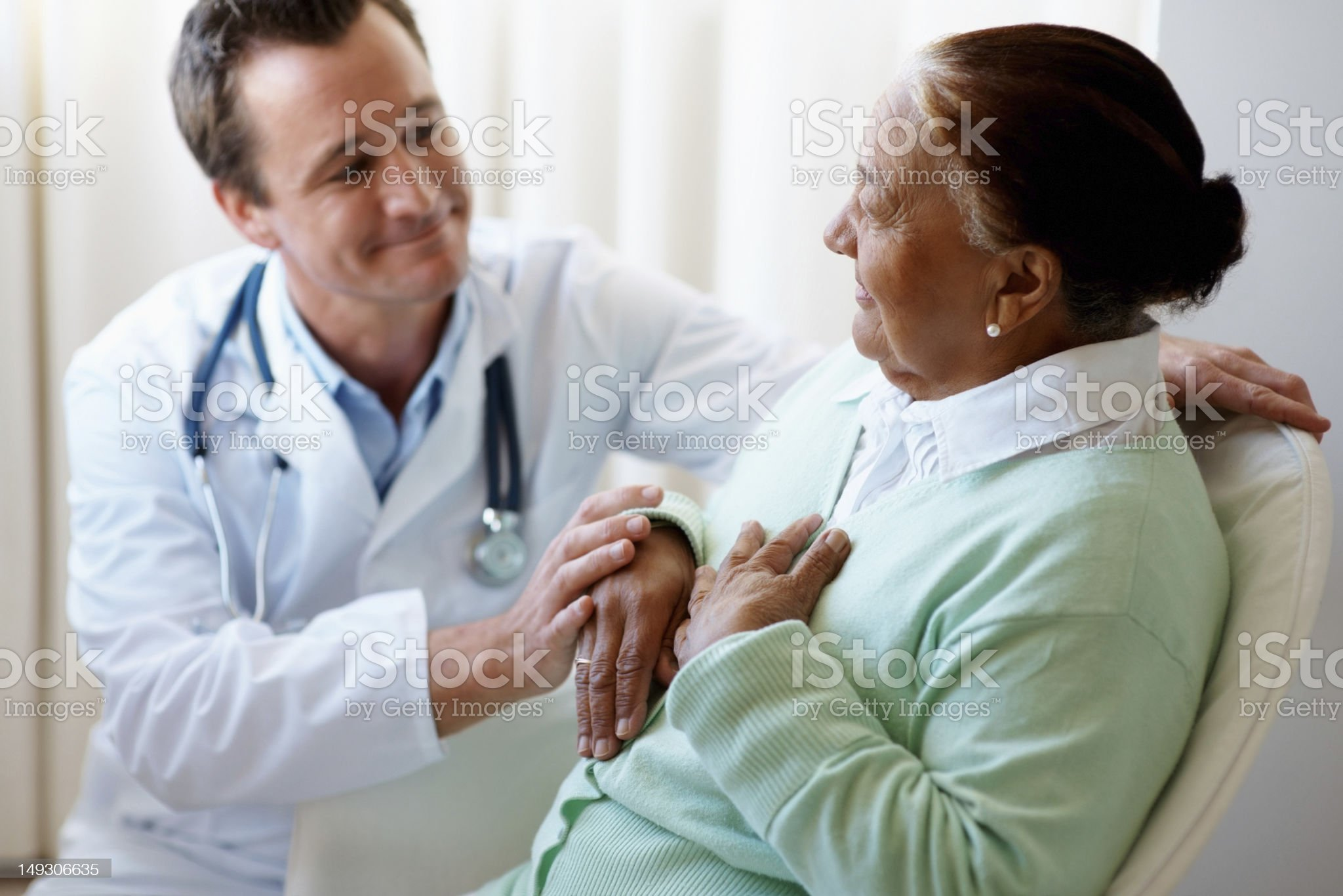 Male doctor visiting a woman at bed royalty-free stock photo