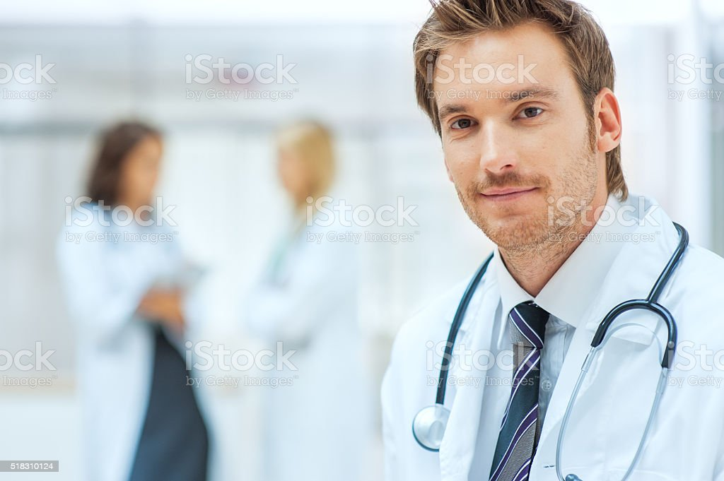 Male doctor with colleagues in the background stock photo