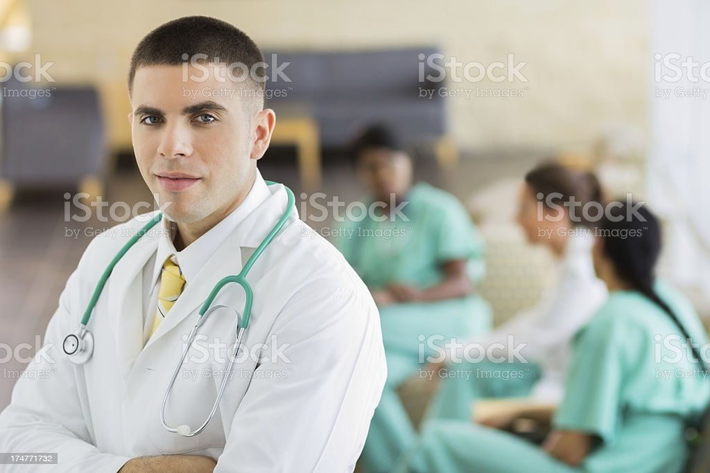 Male doctor with healthcare colleagues in the background stock photo