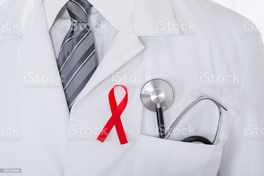 Male Doctor With Stethoscope And Aids Ribbon stock photo