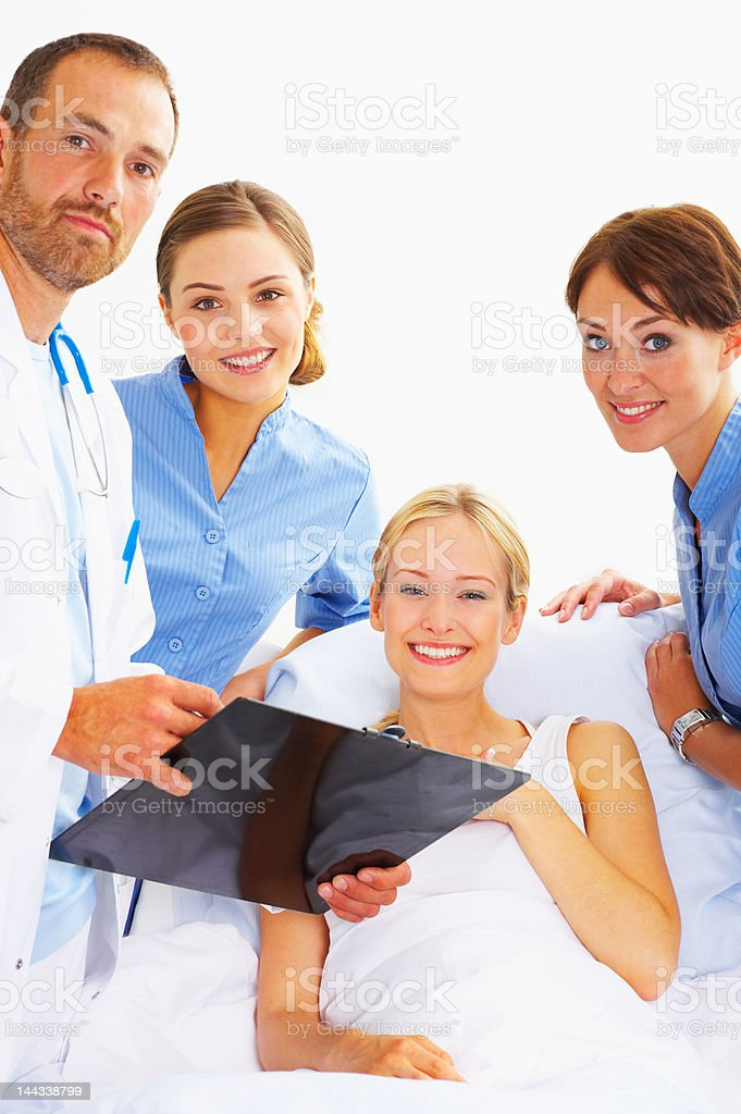 Male doctor with two female nurses examining a patient royalty-free stock photo