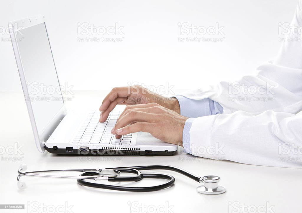 Male doctor working on a laptop stock photo