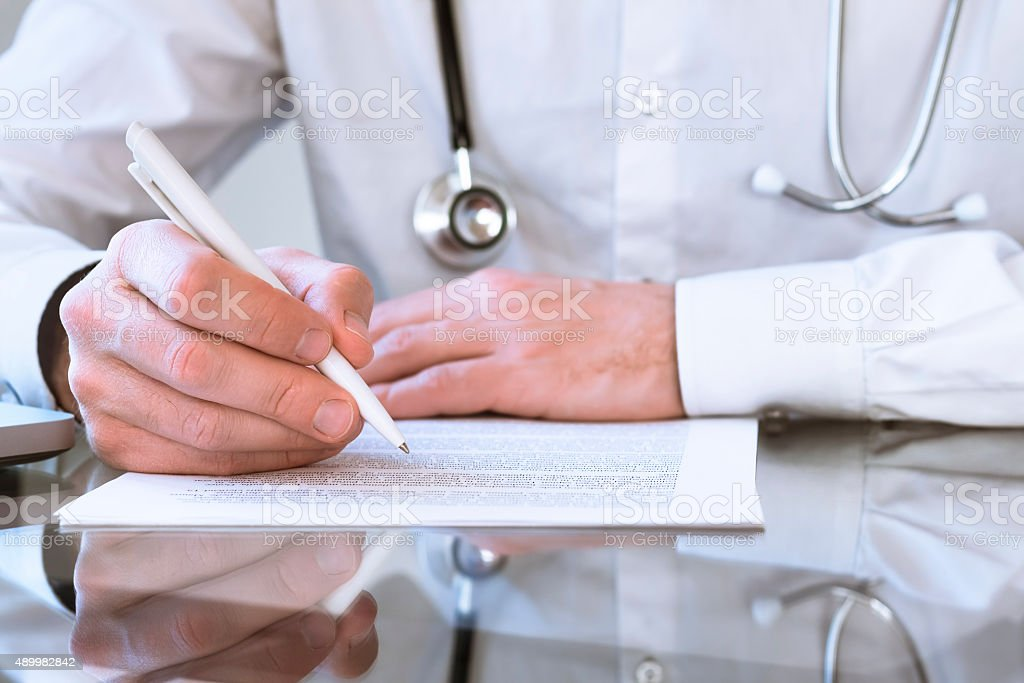 Male doctor writing medical prescription or certificate stock photo