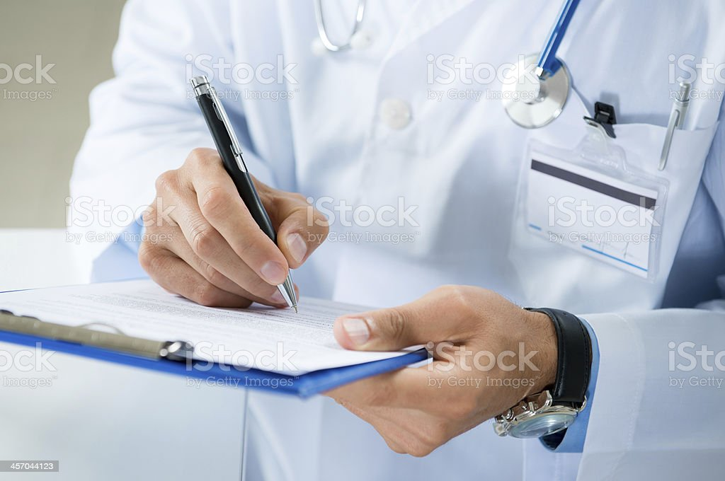 Male Doctor Writing On Medical Document stock photo