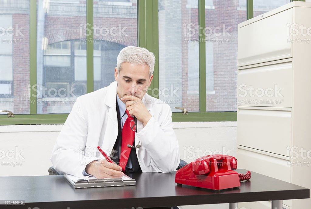 Male Doctor Writing On Notepad royalty-free stock photo