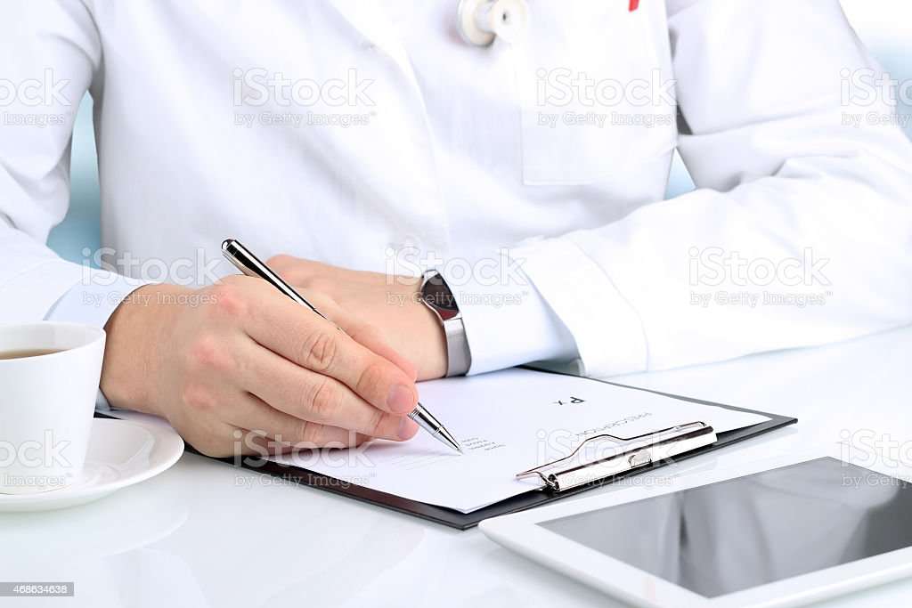 Male doctor writing out a prescription and drinking tea stock photo