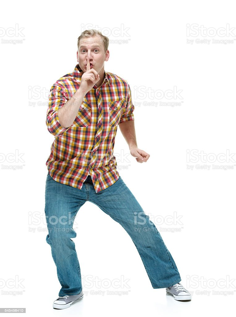 Male doing the be quiet sign stock photo