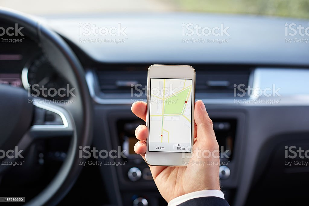Male driver sitting in the car and holding mobile phone stock photo