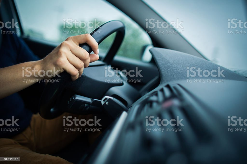 Male driver's hands driving a car stock photo