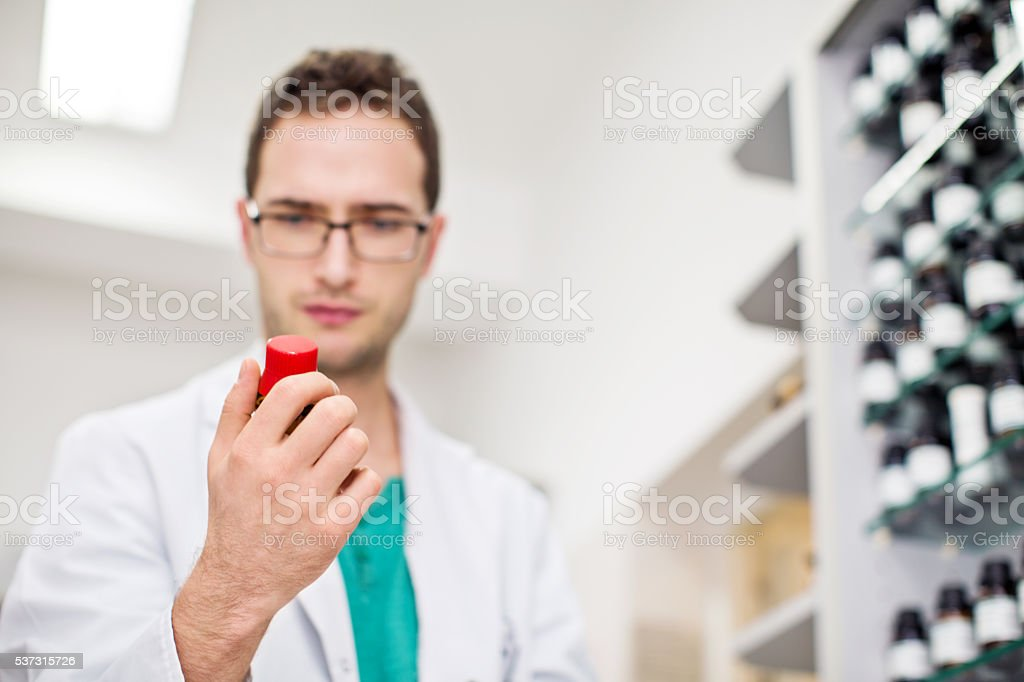 Male druggist checking a bottle of tablets stock photo