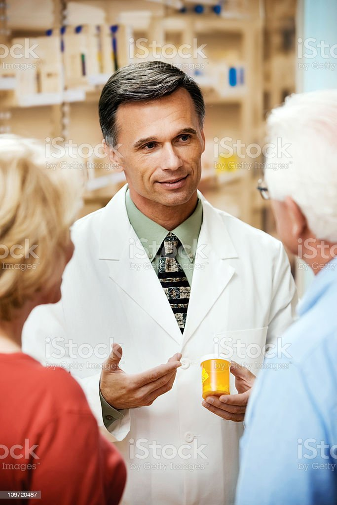 Male Druggist Talking with  Senior Couple Patients stock photo