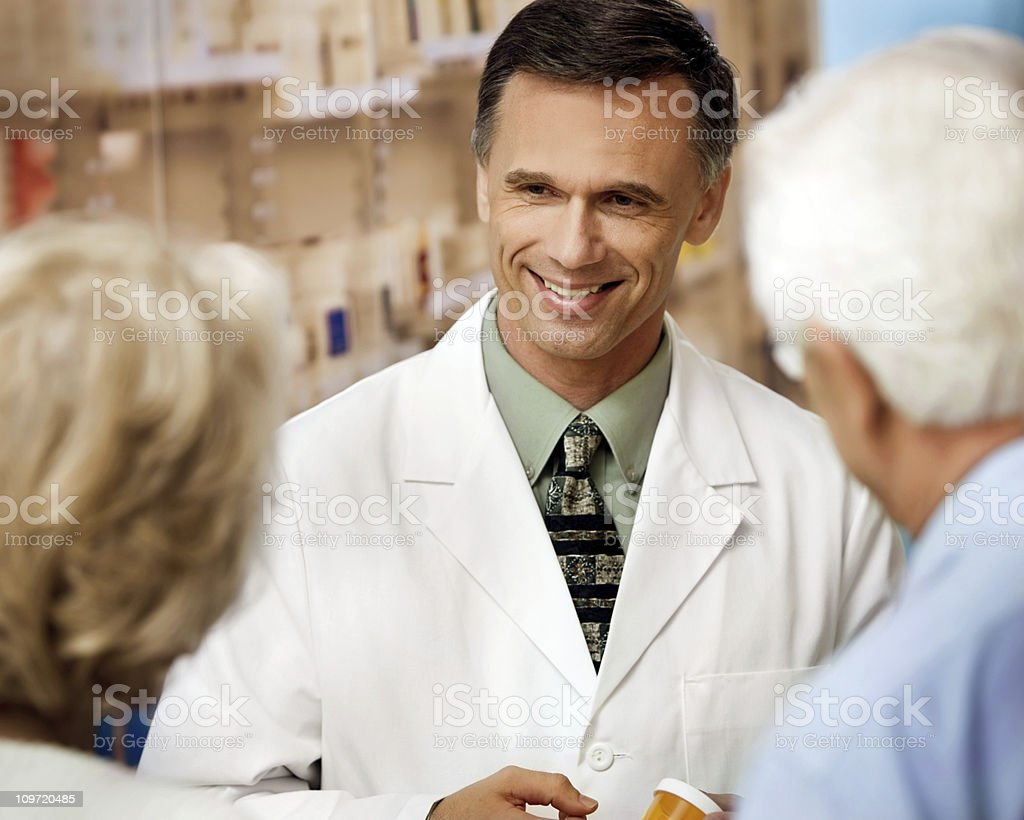 Male Druggist Talking with Senior Couple stock photo