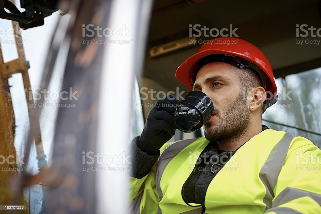 Male earth mover operator drinking coffee royalty-free stock photo