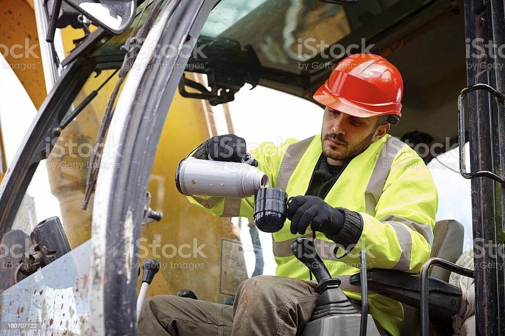 Male earth mover operator taking a coffee break royalty-free stock photo