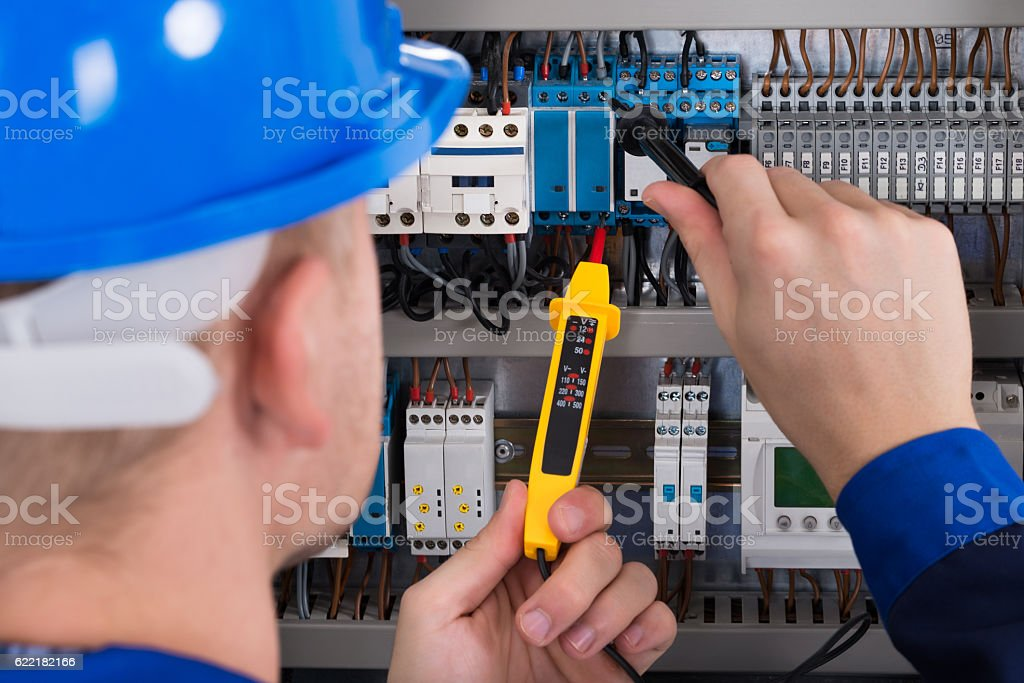 Male Electrician Checking Fusebox stock photo