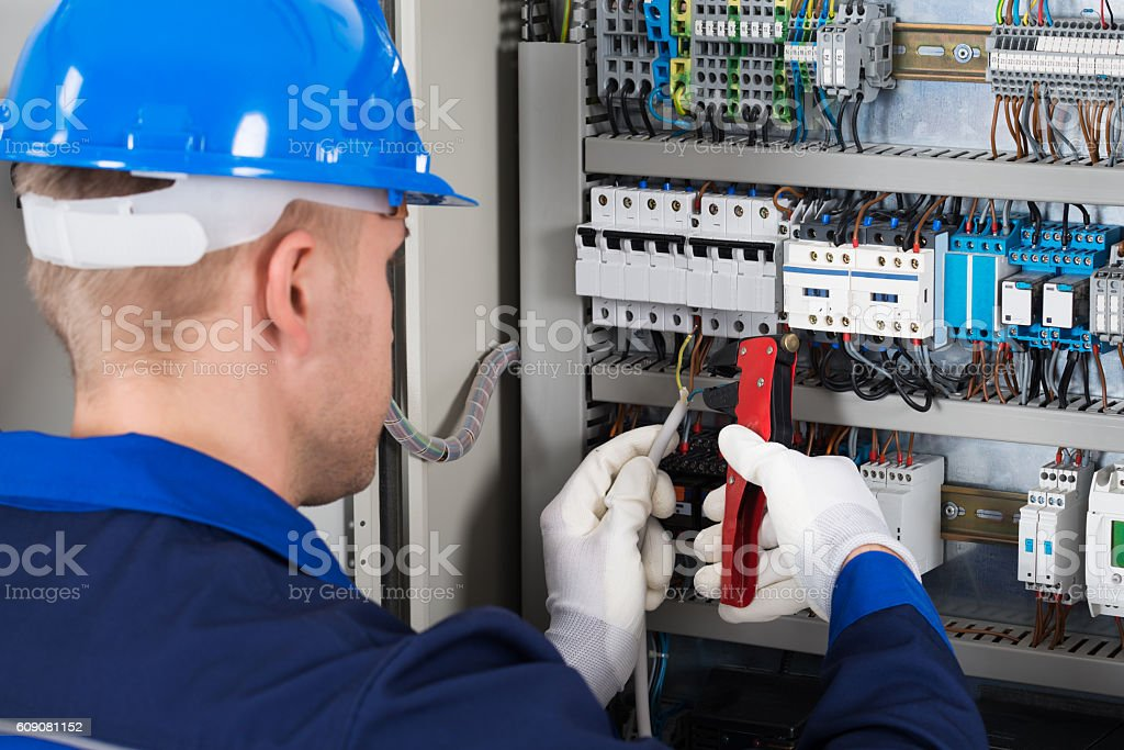 Male Electrician Repairing Fusebox stock photo