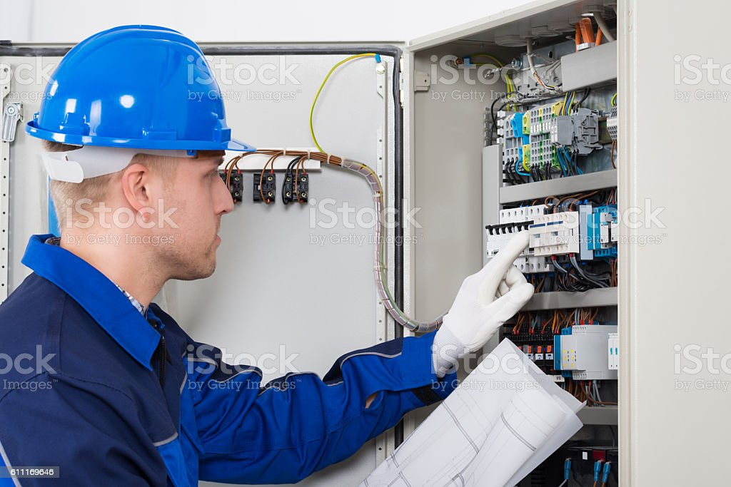 Male Electrician Testing Fusebox stock photo